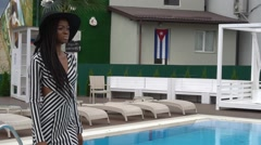 Sexy elegant african american female model in cocktail dress on the pool party - stock footage