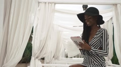 Glamorous african american lady in a striped cocktail dress and black hat using - stock footage