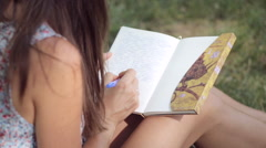 Young woman writes in her diary in the park - stock footage