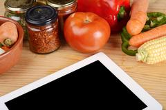 Vegetables and seasonings with a digital tablet. - stock photo
