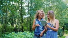 Two young woman walking in the park, laughing: holding the tablet in hands Stock Footage