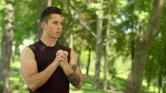 Athletic man stretching wrists in summer park. Attractive man warming up muscle Stock Footage