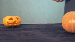 Women with apron carves details of a jack o' lantern on halloween pumpkin Stock Footage