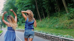 Two female friends having fun walking along the road, waving his arms, rejoicing Stock Footage