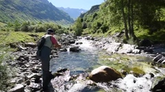Fisherman fly-fishing in Pyrenees mountain river Stock Footage