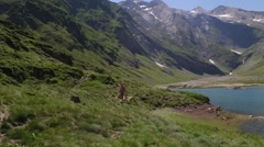 Aerial view of hiker walking by Ossoue lake, Cirque de Gavarnie Stock Footage