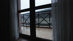 Drops of rain fall on beige tile of porch. Grey sky. Mountains out window - stock footage