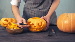 Women with apron carves details of a jack o' lantern on pumpkin Stock Footage