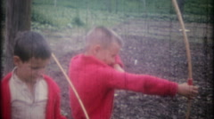 3502 country kids shoot arrows at targets in backyard-vintage film home movie Stock Footage