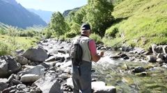 Fisherman fly-fishing in French Pyrenees river Stock Footage