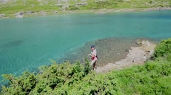 Upper view of fisherman fly-fishing in mountain lake - stock footage