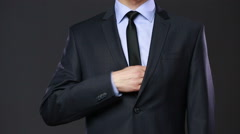 Business man hiding money in pocket on black background. Stock Footage
