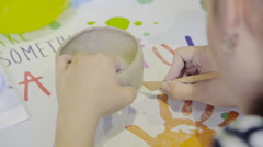 Closeup of hands of young woman ceramist working and finishing pot with clay Stock Footage