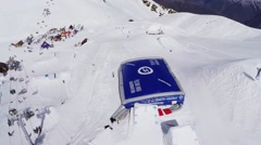 Quadrocopter shoot huge blue trampoline on ski resort. Mountains. Sunny day - stock footage