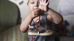 Little blonde boy hold lace of shoe on fingers. Child. Get dressed for walking Stock Footage