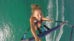 Young Female Tourist in Bikini Parasailing in Blue Sky over Sea Stock Footage