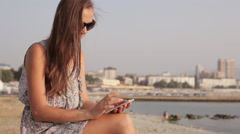 Young woman on seafront with mobile phone Stock Footage