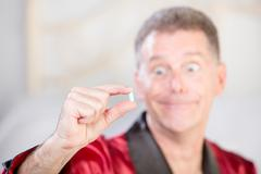 Ecstatic Man with Blue Pill to Combat Erectile Dysfunction Stock Photos