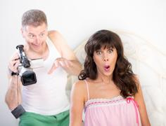 Enthusiastic Man Tries to Shoot Video of Pretty Woman in Bedroom Stock Photos