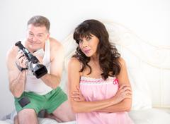 Enthusiastic Man with Camera on Bed with Pretty Woman Kuvituskuvat
