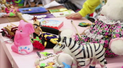 Many toys lying on table, children playing games at kindergarten or orphan home Stock Footage