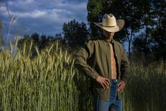 Portrait of rustic man in cowboy hat with unbuttoned shirt Stock Photos