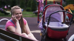 Young mother speak to phone on playground. Red baby carriage. Kids. Smile Stock Footage