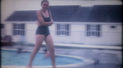 Shy, pretty young girl diving in the hotel pool, 3505 vintage film home movie Stock Footage