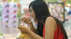 Young Asian Lady eating in mall food court 4k UHD (3840x2160) Stock Footage
