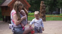 Young mother hold baby in sling, play with son in sandbox. Playground. Family - stock footage