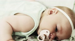 Adorable little baby lie on sofa with baby dummy. Cute. Looking in camera Stock Footage