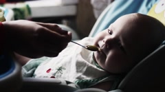 Mother feeding adorable baby at children table by puree. Motherhood. Love Stock Footage