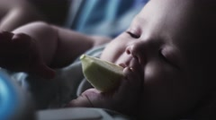Adorable cute baby sit at children table eating pear. Blue eyes. Look in camera Stock Footage