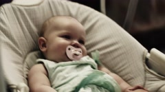 Adorable little baby sway on swing in apartment. Baby dummy. Child. Smile Stock Footage