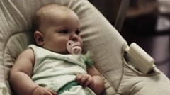 Adorable little baby sway on swing in apartment. Baby dummy. Child. Relax Stock Footage