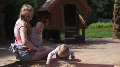 Young mother hold baby in sling, playing with son in sandbox. Playground - stock footage