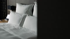A double bed with white sheets in a hotel room-Dan Arkistovideo