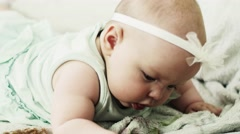 Adorable little baby lie on sofa put baby dummy in mouth. Cute. Childhood Stock Footage