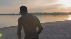 Silhouette Of Man On Beach Running SlowMo On Sand Into Sunset Stock Footage