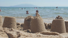 Sand castles on tropical beach close up, people and children enjoy in sea water. Stock Footage