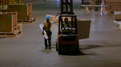 A dark, wide shot of workers using a forklift to move a wooden structure. Stock Footage