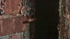 A medium shot of a rusty door handle on a paint chipped door. The handle moves Stock Footage
