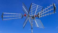 Tv antenna against blue sky Stock Photos