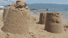 Sand castles on beach close up, people are bathing on sea water in background. Stock Footage