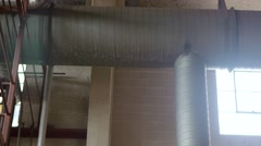A pan shot of a large air duct on the ceiling of an abandoned factory. - stock footage
