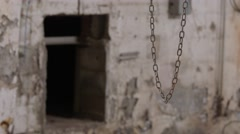 A wide shot of a chain swinging in from of a paint chipped wall. Stock Footage
