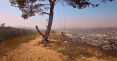 Young woman on top of mountain tree swing, swinging over Los Angeles cityscape Stock Footage