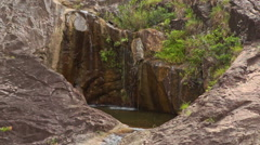 Small Streams Fall into Round Hole Pool from Rock Tops Stock Footage