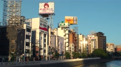 Fukuoka - View of river bank with buildings and signboards in evening light. 4K Stock Footage