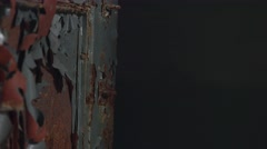 A close up shot of an old rusty door with paint peeling as a creepy hand grabs Stock Footage